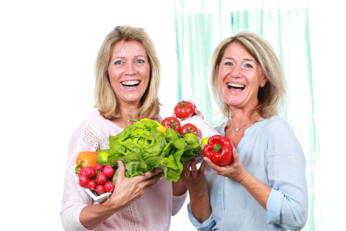Two happy middle age woman with different vegetables and salad