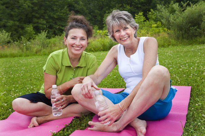 Due signore mature condividono una risata dopo la lezione di yoga.
