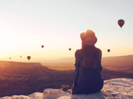 View from the back of a girl in a hat sits on a hill and looks at air balloons in Cappadocia in Turkey.