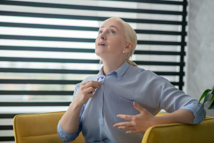 Visit doctor. Blond-haired adult woman sitting in a yellow armchair telling gesturing serious.