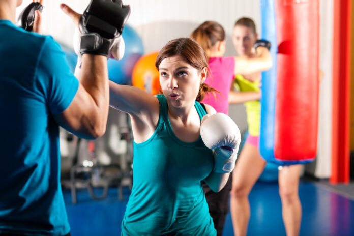 Woman Boxer hitting the sandbag, her trainer is assisting