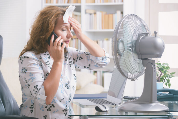 Woman suffers from heat while working in the office and tries to cool off by the fan