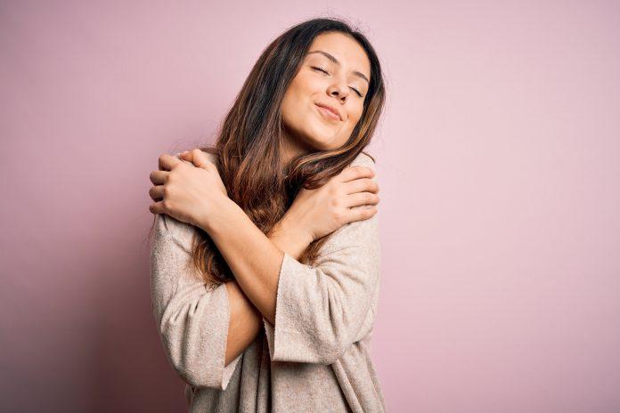 Giovane bella donna bruna che indossa un maglione casual in piedi su sfondo rosa Abbracciare se stessi felice e positivo, sorridendo fiducioso. Amore per se stessi e cura di sé