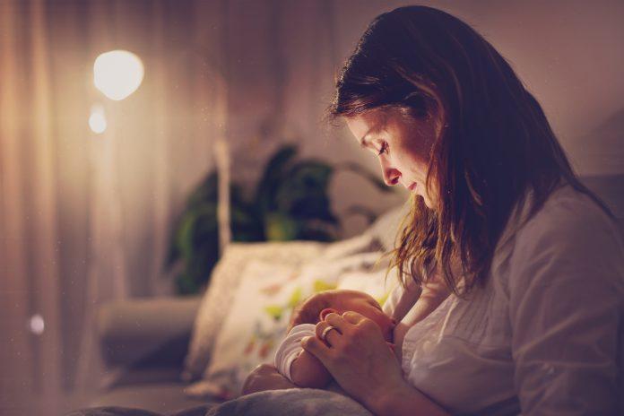 Jeune et belle mère, allaitant son nouveau-né, un garçon, la nuit, lumière tamisée. Maman allaitant son bébé