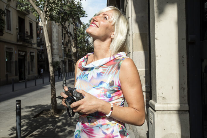 Young blond woman taking photos in the city