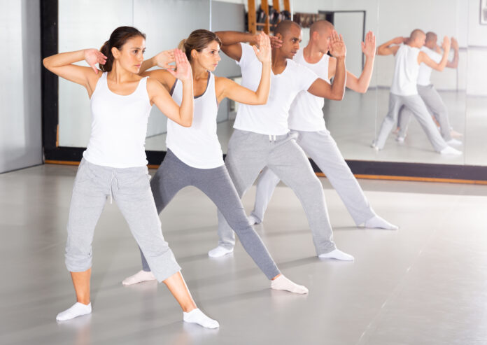 Young men and women mastering martial arts techniques for self-defense at practice in training room