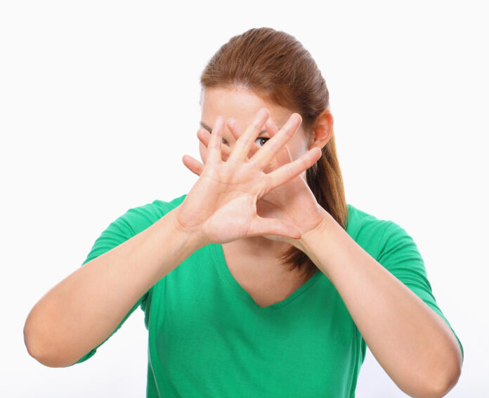 Young Woman blocking face with hands.
