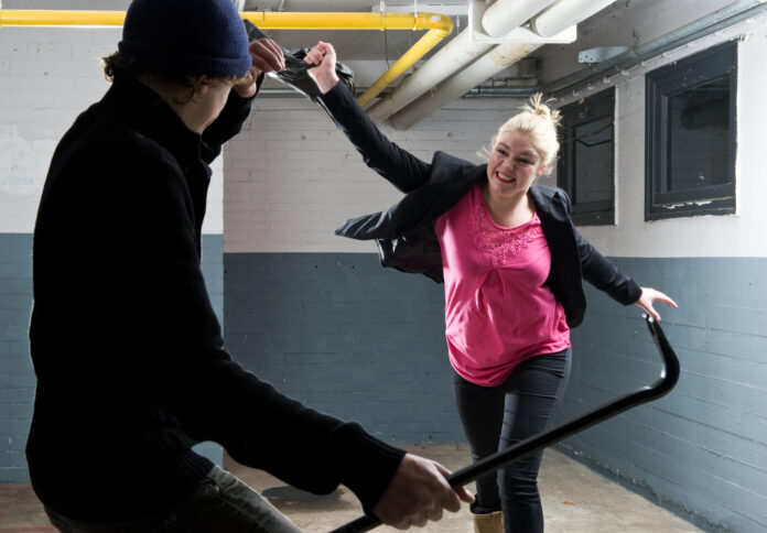 Young woman defending herself with her purse  against a criminal armed with a crowbar.