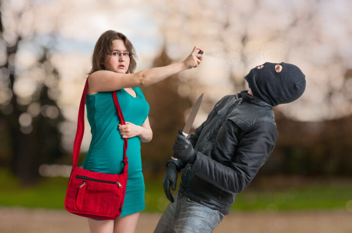 Young woman is defending with pepper spray against armed thief with knife.
