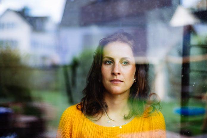 Une jeune femme regarde pensivement et tristement par la fenêtre le jardin avec des jouets d'enfants.