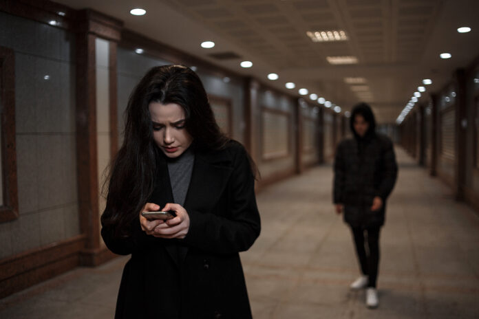 a young beautiful woman walks through an underground passage at night, followed by a man in dark clothing with a hood on his head. a woman tries to dial the number of the rescue service on the phone