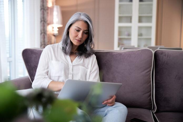 Erwachsene nachdenkliche Frau, die einen Laptop benutzt, während sie auf einem Sofa sitzt