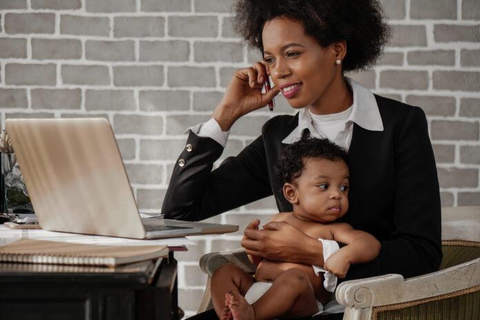 femme d'affaires afro-américaine s'occupant de son petit garçon tout en travaillant à la maison