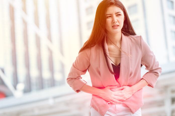 Asian woman front stomach painful sign of Ovarian Endometriosis and Chocolate Cyst syndrome.