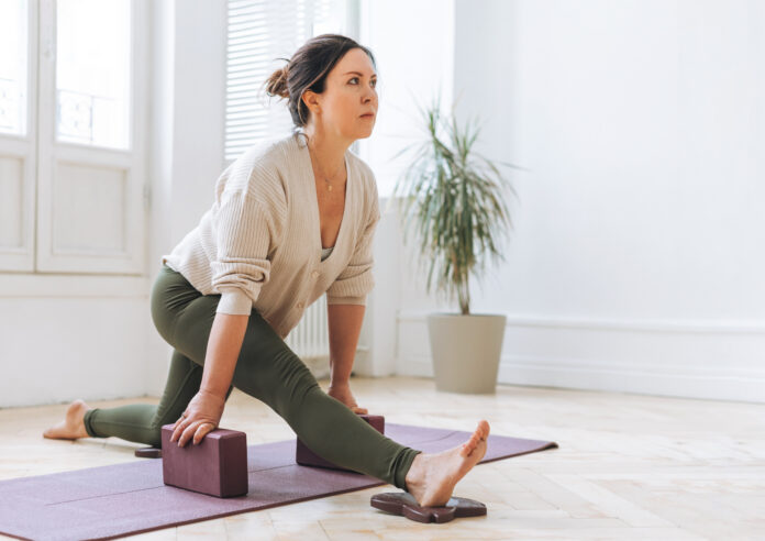 Attractive middle aged brunette woman in sportswear ptactice yoga with equipment in the light studio