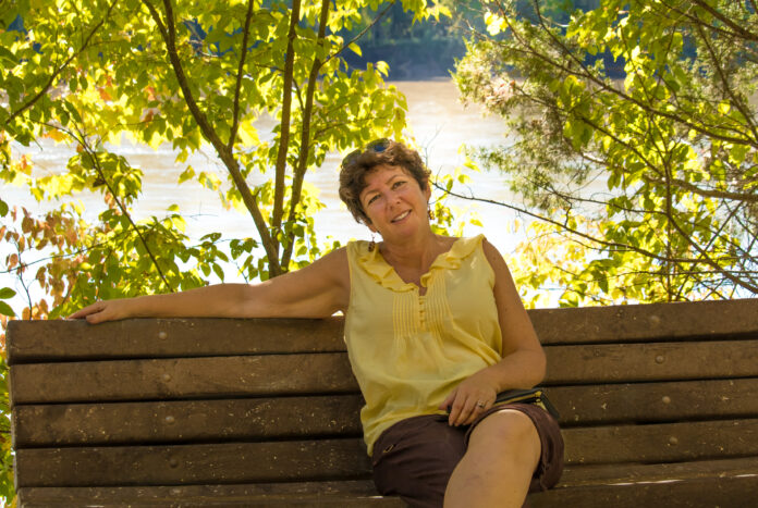 Attractive middle aged woman sitting on a wooden bench in the fall, smiling; river in the background; Missouri, Midwest