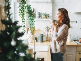 Attractive femme souriante aux cheveux bouclés en chemise à carreaux avec une tasse de thé près de la fenêtre d'une cuisine lumineuse à la maison. Période de Noël