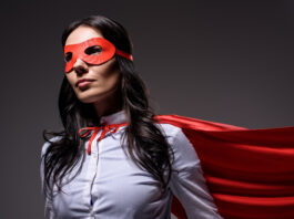 atractiva mujer de negocios con capa roja y máscara aislada sobre negro