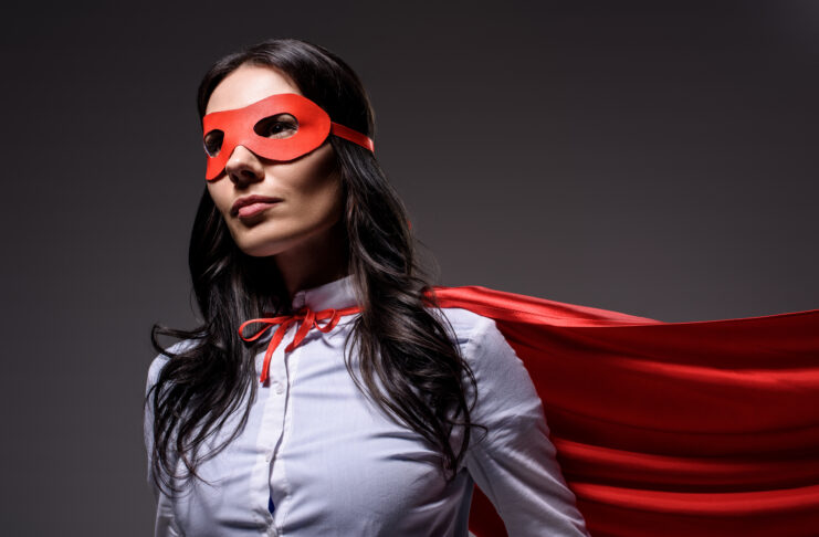 attractive super businesswoman in red cape and mask isolated on black