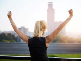 Portrait de dos d'une femme d'affaires debout face à la vue de la ville et levant les mains en signe de victoire.