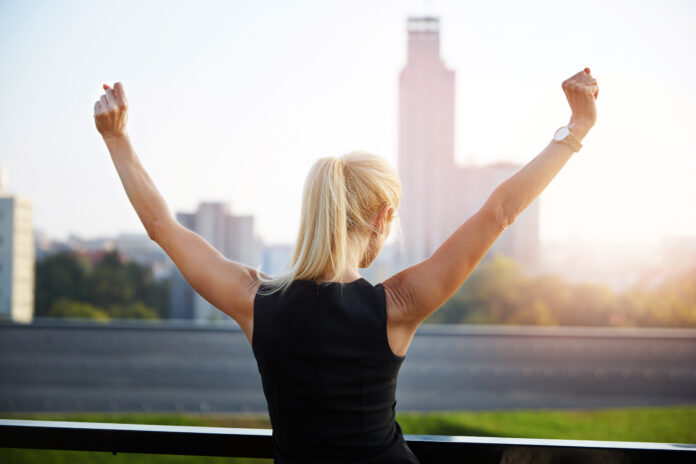 Portret op de rug van een zakenvrouw die frontaal naar de stad kijkt en haar handen in een overwinningsgebaar opheft.
