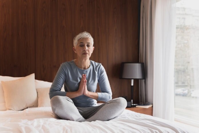 Beautiful senior woman meditating in her bedroom, Healthy morning routine and yoga concept