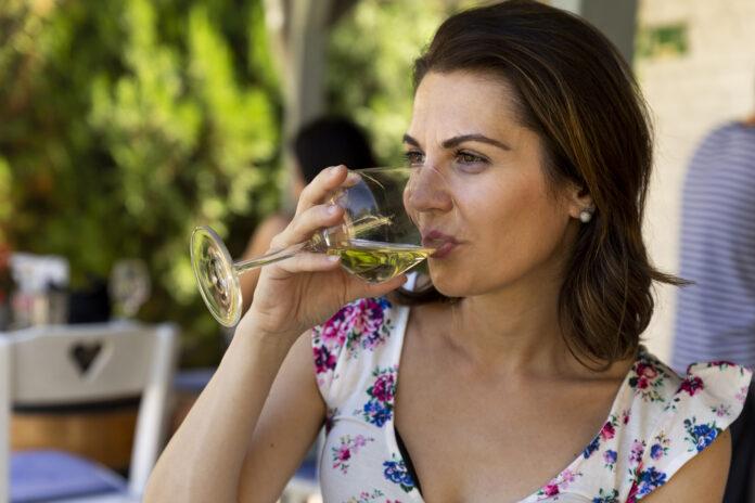 Schöne Frau trinkt Weißwein aus Weinglas im Restaurant