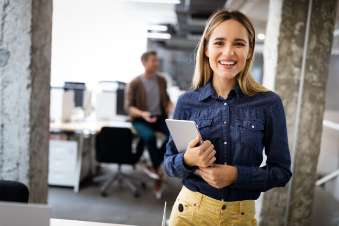 Beautiful young business woman holding tablet computer in office