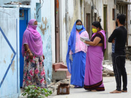 Beawar, Rajasthan, India - April 20, 2020: Anganwadi workers wearing protective face mask interacts with a woman during a door-to-door survey to check the spread of novel coronavirus, at slum area in Beawar.