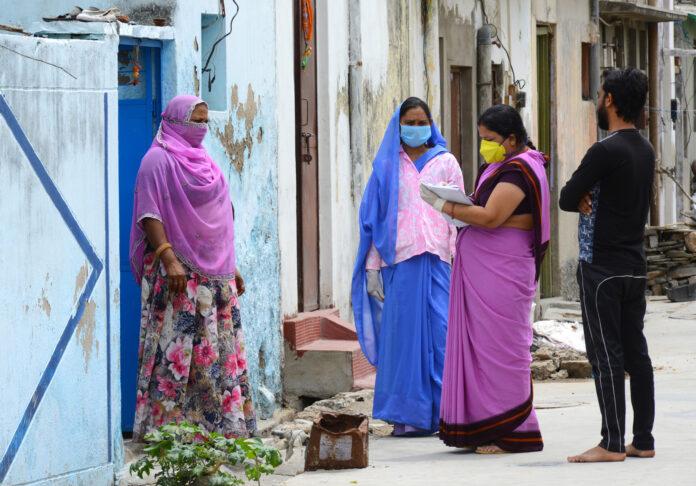 Beawar, Rajastán, India - 20 de abril de 2020: Trabajadores anganwadi con mascarilla protectora interactúan con una mujer durante una encuesta puerta a puerta para comprobar la propagación del nuevo coronavirus, en un barrio marginal de Beawar.