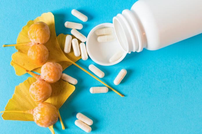 Bottle of matural pills for memory. Ginkgo biloba leaves. Blue background
