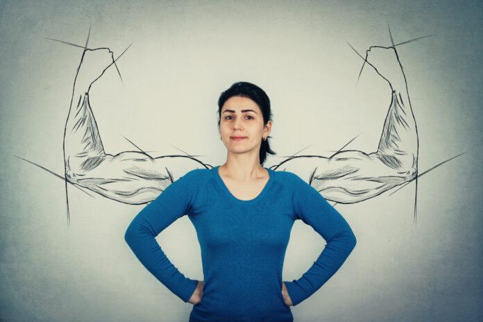 Tapfere Frau, Hände auf den Hüften, vor Ängsten wie ein mächtiger Held als muskulöse Arme Skizzen an der Wand zeigt ihre innere Stärke. Starkes Mädchen zeigt große Bizeps. Selbstverteidigung und Vertrauen Konzept.