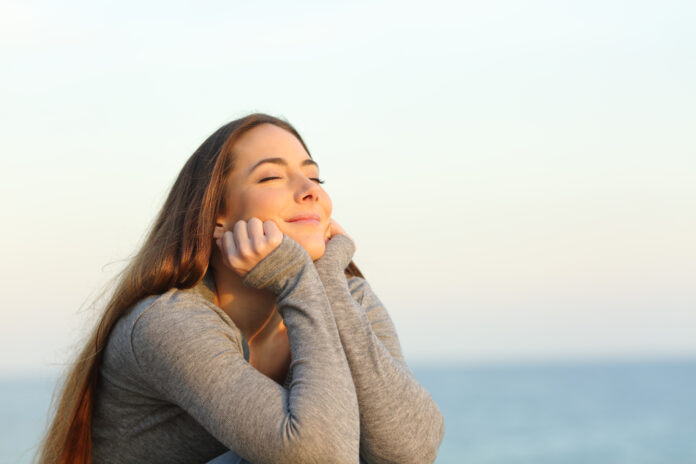 Candid woman breathing fresh air relaxing sitting on the beach at sunset