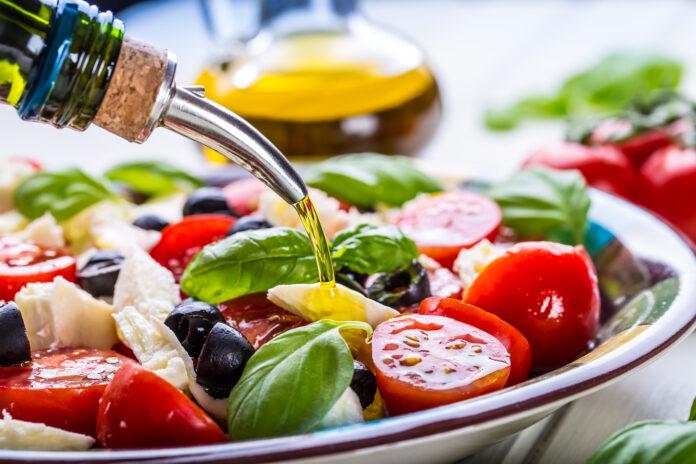 Caprese. Caprese-Salat. Italienischer Salat. Mediterraner Salat. Italienische Küche. Mediterrane Küche. Tomate-Mozzarella-Basilikum-Blätter, schwarze Oliven und Olivenöl auf Holztisch. Rezept - Zutaten