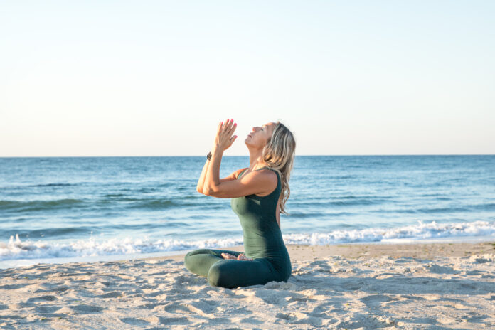 caucasian healthy woman with beautiful body doing yoga at sunrise on the beach, yoga poses
