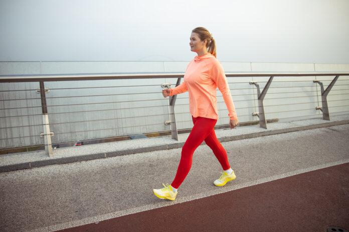 Charming sporty lady having race walking training outdoors stock photo