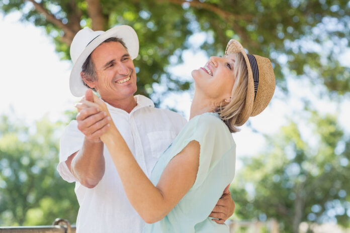 Cheerful couple dancing outdoors against trees