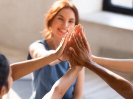 De vrolijke diverse jonge meisjeszitting samen in sportenstudio vóór begint opleiding die hoge vijf geven voelt gelukkig en gezond, dichte omhoog nadruk op handen. Respect en vertrouwen, viering en amityconcept
