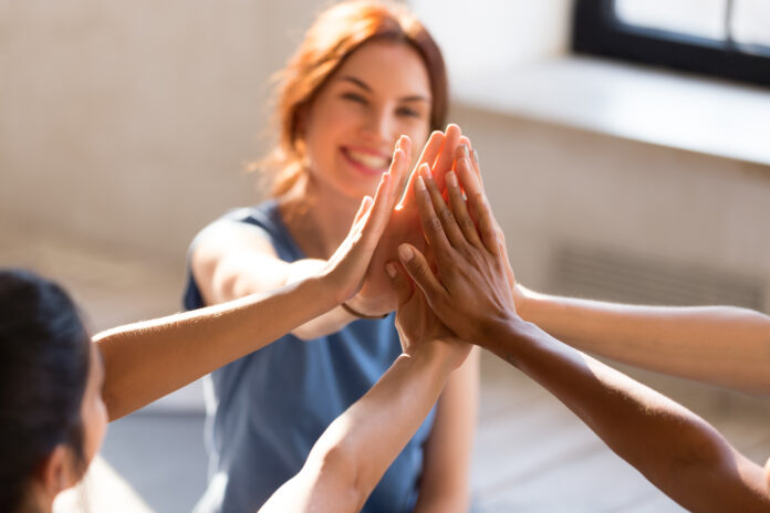 Fröhlich diverse junge Mädchen sitzen zusammen in Sportstudio vor beginnt Training geben High Five fühlen sich glücklich und gesund, Nahaufnahme Fokus auf Hände. Respekt und Vertrauen, Feier und Freundschaft Konzept