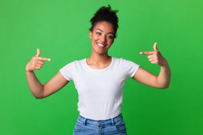 Kies Mij. Positieve zwarte dame die op zich het dragen van leeg wit t-shirt, exemplaarruimte, groene studiomuur richt