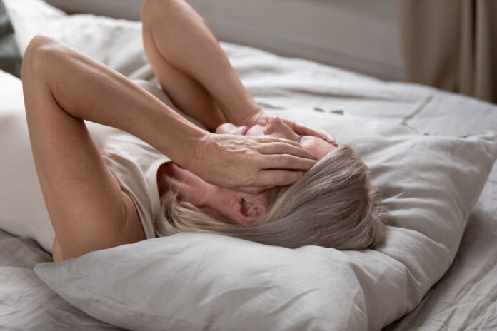 Close up 60s female awaken lying on pillow in bed at home cover face with hands feels exhausted lack of energy caused by chronic sleeplessness woman goes through divorce life or health trouble concept