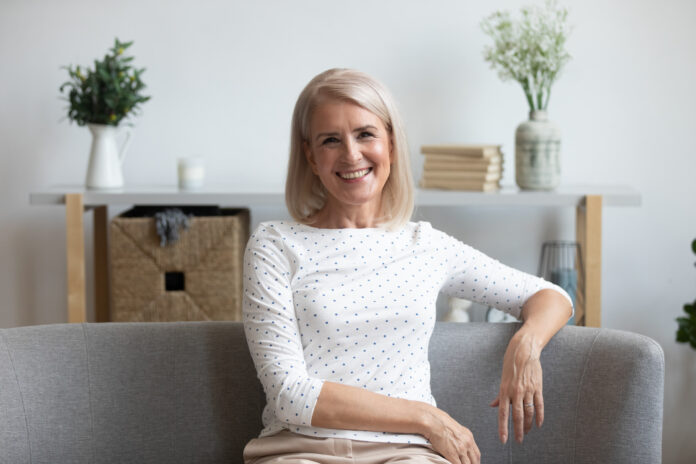 Close up headshot portrait of smiling positive elderly woman sit on couch in living room look at camera, happy middle-aged female pensioner rest relax on cozy sofa at home posing for picture indoors