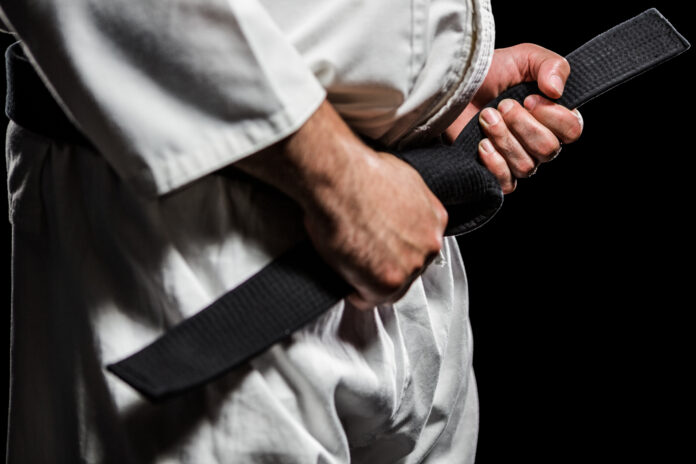 Close-up of fighter tightening karate belt on black background
