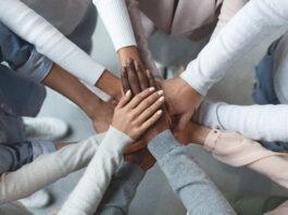 Sluit omhoog van internationaal bedrijfsteam dat eenheid toont met het zetten van hun handen samen bovenop elkaar. Concept van teamwork, hoogste mening