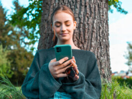Confident smiling teenage woman leaning on tree in the garden, reading messages on her mobile phone, smiling confident and happy. Young women social media lifestyle concept shot.