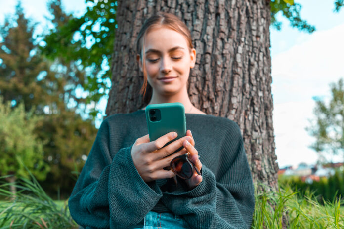 Donna adolescente sorridente e fiduciosa appoggiata all'albero in giardino, leggendo i messaggi sul suo telefono cellulare, sorridendo fiduciosa e felice. Colpo di concetto di stile di vita di media sociali delle giovani donne.