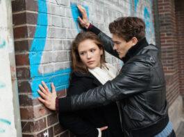 Conflit de couple dans la rue, un homme agressif tient une jeune femme triste appuyée sur un mur, violence, crime sexuel, vie urbaine négative dans la rue, problème de relation.