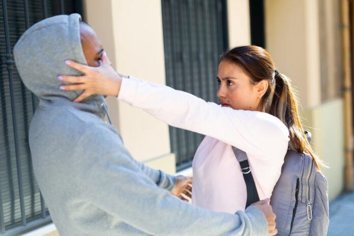 Decidida joven latina que utiliza técnicas de Krav Maga para protegerse del hombre atacante en la calle de la ciudad. Concepto de autodefensa femenina