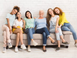 Diverse Women Of Different Age Sitting On Sofa Smiling To Camera Indoor. Support Group Concept