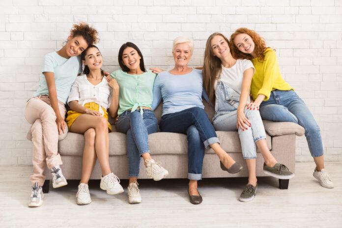Diverses femmes d'âges différents assises sur un canapé et souriant à la caméra en intérieur. Concept de groupe de soutien